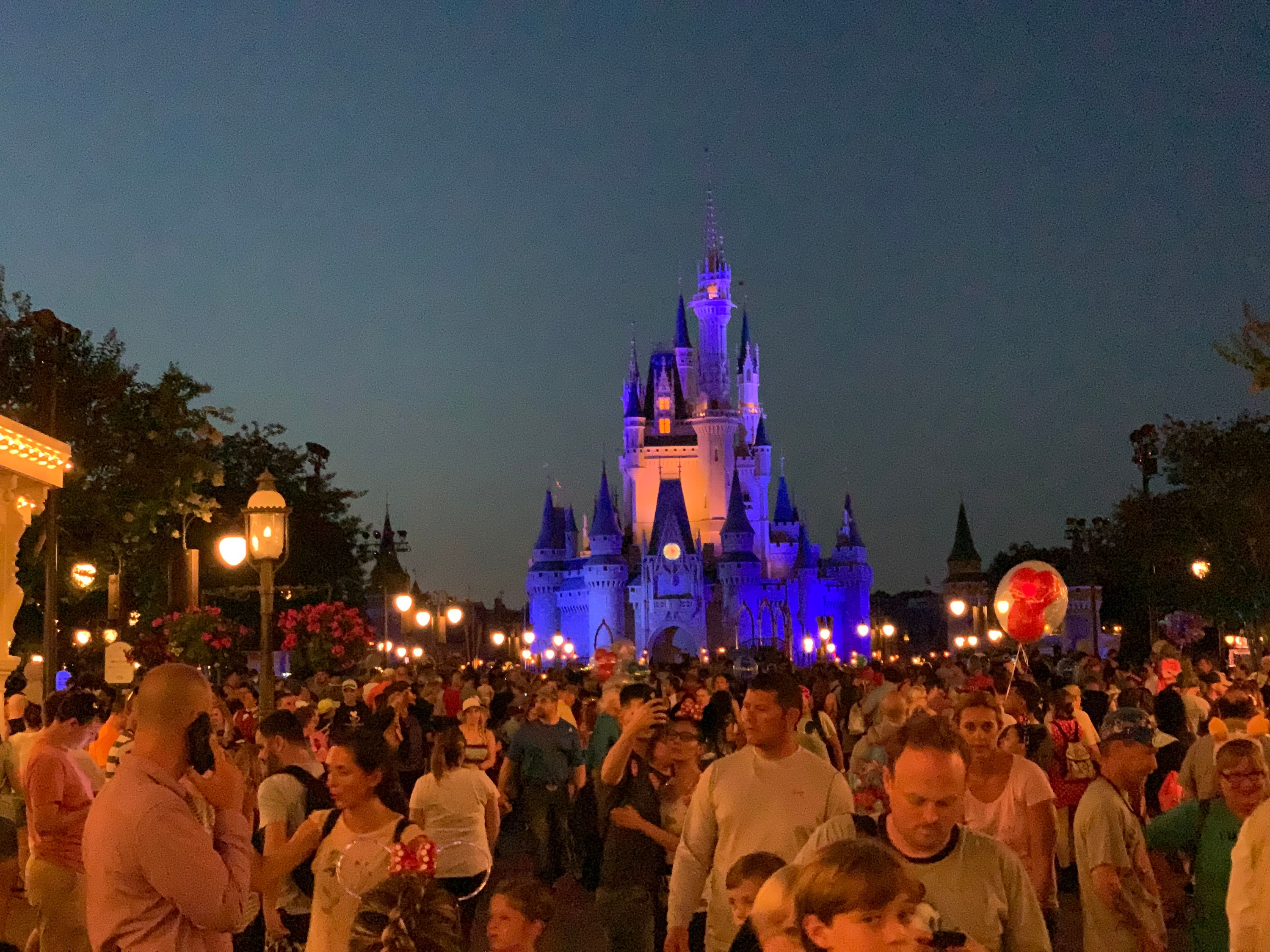 Cinderella's Castle is lit up at night behind a crowd of people on Disney World's Main Street USA.